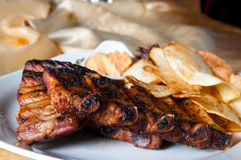 Grilled pork ribs. With potatoes chips. A classic cuisine Stock Image