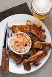 Grilled pork ribs in barbecue sauce and honey with sauerkraut and beer on a white plate. Snack to beer on a light stone table. Top. View Stock Image