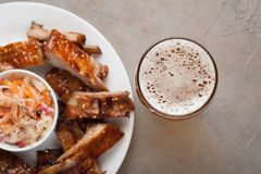 Grilled pork ribs in barbecue sauce and honey with sauerkraut and beer on a white plate. Snack to beer on a light stone table. Top. View Royalty Free Stock Photo