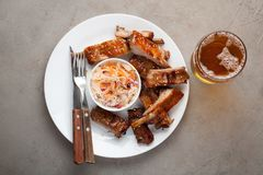 Grilled pork ribs in barbecue sauce and honey with sauerkraut and beer on a white plate. Snack to beer on a light stone. Table. Top view with copy space Stock Photo