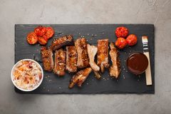 Grilled pork ribs in barbecue sauce and honey with sauerkraut and roasted tomatoes on a black stone Board. Snack to beer. On a light stone background. Top view Royalty Free Stock Photography