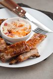 Grilled pork ribs in barbecue sauce and honey with sauerkraut on white plate. Snack to beer on a light stone table.  Royalty Free Stock Photography
