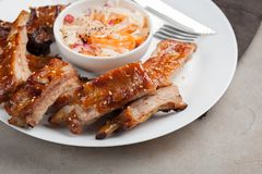 Grilled pork ribs in barbecue sauce and honey with sauerkraut on white plate. Snack to beer on a light stone table.  Stock Photography