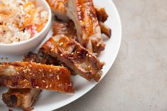 Grilled pork ribs in barbecue sauce and honey with sauerkraut on white plate. Snack to beer on a light stone table, Top view.  Stock Photos