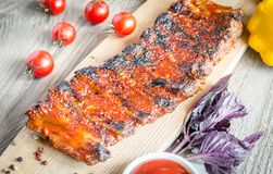 Grilled pork ribs in barbecue sauce. On the wooden table Stock Image