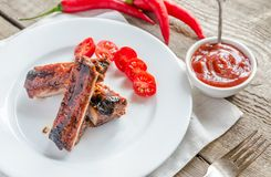 Grilled pork ribs in barbecue sauce. On the wooden table Stock Images