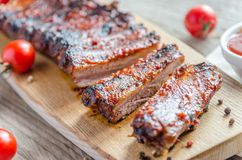 Grilled pork ribs in barbecue sauce. On the wooden table Royalty Free Stock Photos