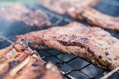 Grilled pork ribs on barbeque. Pork ribs being grilled over charcoal. Ribs is well cooked, close shot Royalty Free Stock Photo
