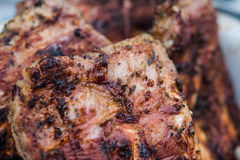 Grilled pork ribs on barbeque. Pork ribs being grilled over charcoal. Ribs is well cooked, close shot Royalty Free Stock Photos