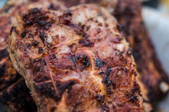 Grilled pork ribs on barbeque. Pork ribs being grilled over charcoal. Ribs is well cooked, close shot Stock Images