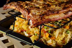 Grilled pork ribs with braised cabbage on a baking sheet. royalty free stock image