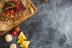 Grilled pork ribs, buckwheat with mushroom and tomatoes on old vintage wooden cutting board. Flat lay, top view. Copy space. Grilled pork ribs, buckwheat with Stock Image