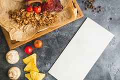 Grilled pork ribs, buckwheat with mushroom and tomatoes on old vintage wooden cutting board. Flat lay, top view. Paper card with c. Grilled pork ribs, buckwheat Stock Photo