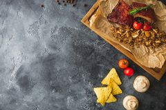 Grilled pork ribs, buckwheat with mushroom and tomatoes on vintage wooden cutting board on dark table. Flat lay, top view. Copy sp. Grilled pork ribs, buckwheat Royalty Free Stock Photo