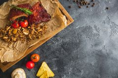 Grilled pork ribs, buckwheat with mushroom and tomatoes on vintage wooden cutting board. Flat lay, top view. Copy space. Grilled pork ribs, buckwheat with Royalty Free Stock Photography
