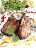 Grilled pork ribs. Close up of grilled pork ribs served with fried onions and garlic Stock Image
