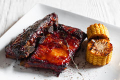 Grilled pork ribs with corn on white plate Royalty Free Stock Image