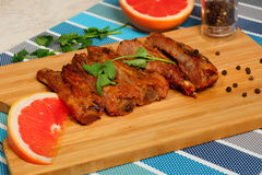 Grilled pork ribs and cut red grapefruit. Grilled pork ribs on a cutting board.black pepper and coriander, red grapefruit Royalty Free Stock Photography