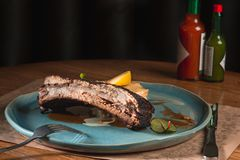 Grilled pork ribs on dark plate Stock Images