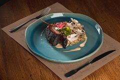 Grilled pork ribs on dark plate. The grilled pork ribs on dark plate on wooden table Royalty Free Stock Images