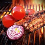 Grilled pork ribs on the flaming grill. Stock Photography