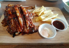 Grilled pork ribs with French fries. Grilled pork ribs with French fries served on a cutting board Stock Photo