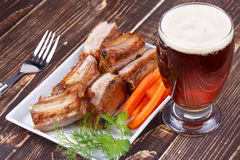 Grilled pork ribs and glass of beer. On wooden background Royalty Free Stock Image