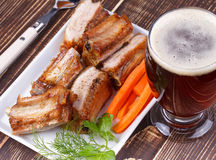 Grilled pork ribs and glass of beer on wooden background Royalty Free Stock Photos