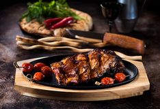Grilled pork ribs. With and grilled cherry tomatoes, fresh greens, and bread lavash Stock Images