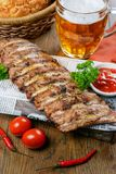 Grilled pork ribs. On paper sheet garnished to beer Stock Photos