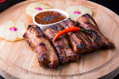 Grilled pork ribs. Served with pineapple on a board Stock Images