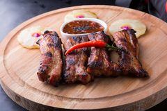 Grilled pork ribs. Served with pineapple on a board Stock Photo
