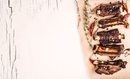 Grilled pork ribs with herbs top view. Top view of grilled pork ribs with herbs on the piece of brown crafted paper on white wooden background with cracked paint Stock Image
