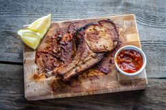 Grilled pork ribs. With lemons and barbecue sauce Royalty Free Stock Photo
