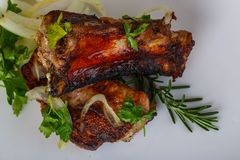 Grilled pork ribs. With onion, parsley and rosemary Royalty Free Stock Photography