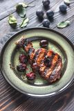 Grilled pork ribs with plum sauce. Grilled pork ribs with plums on the plate Royalty Free Stock Photography