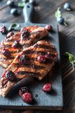 Grilled pork ribs in plum sauce. On the wooden board Stock Photography