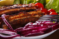 Grilled pork ribs with red onions and tomatoes on a plate Stock Photos