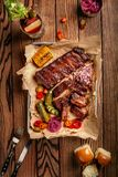 Grilled pork ribs served with grilled corn, salat, bbq sauce, salt pepper and cucumber on parchment paper on a wooden Stock Image