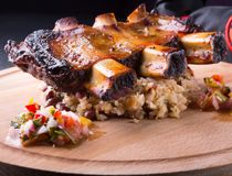 Grilled pork ribs. Served with rice on a wooden board Stock Photos