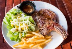 Grilled pork ribs steak well-done with french fries and vegetabl Stock Images