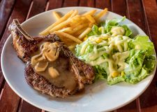 Grilled pork ribs steak well-done with french fries and vegetabl Royalty Free Stock Images