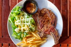 Grilled pork ribs steak well-done with french fries and vegetabl Stock Photography