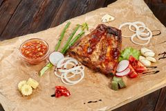 Grilled pork ribs, sweet and sour sauce. Meat with vegetables stock photos