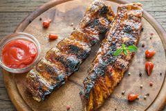 Grilled pork ribs with tomatoe sauce on the wooden board Royalty Free Stock Images