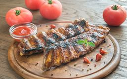 Grilled pork ribs with tomatoes on the wooden board Stock Photo