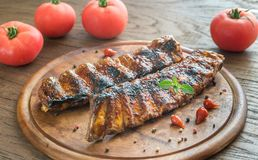 Grilled pork ribs with tomatoes on the wooden board Stock Images
