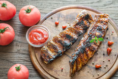 Grilled pork ribs with tomatoes on the wooden board Royalty Free Stock Photos