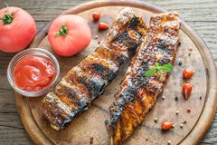 Grilled pork ribs with tomatoes on the wooden board Stock Photography