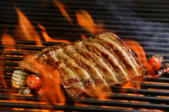 Grilled pork ribs with vegetable. On the flaming grill Stock Photo